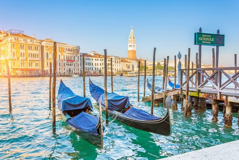 Grand Canal gondoler på pir - egen service för gondol och San Giorgio Maggiore kyrka royaltyfri bild
