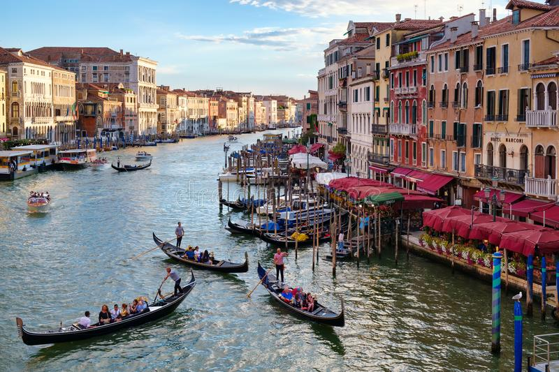 The Grand Canal in Venice at sunset with gondolas and old colorful buildings. VENICE,ITALY - JULY 25,2017 : The Grand Canal in Venice at sunset with gondolas and royalty free stock image