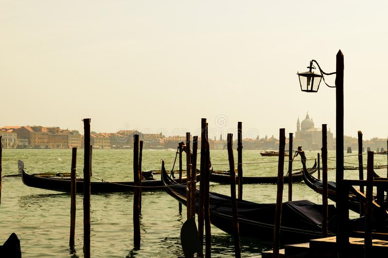 Grand canal in Venice during sunset. Grand canal with silhouettes of two swimming gondolas and Basilica Santa Maria della Salute in Venice during sunset and very royalty free stock images