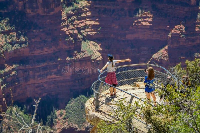Grand Canyon, Arizona U.S.A., 14 GIUGNO, 2018: Una viandante di due donne sta stando su una scogliera ripida che contiene la vist immagine stock