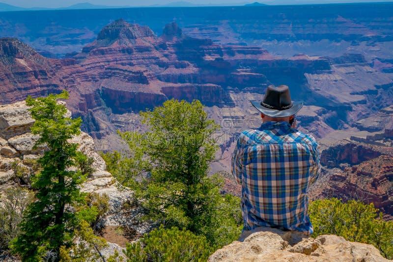 Grand Canyon, o Arizona EUA, JUNHO, 14, 2018: Opinião homem não identificado que veste uma camisa e um chapéu de manta, usando se imagem de stock