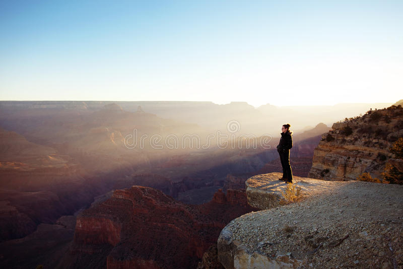Grand Canyon Sunrise. Woman looking out over the grand canyon at sunrise on a clear day royalty free stock image