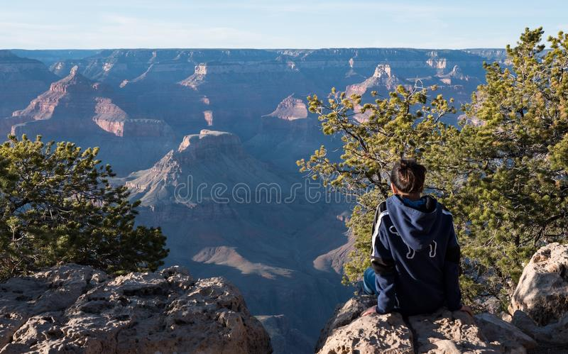 Young Girl sat looking out enjoying the sunset view of the grand canyon stock photography