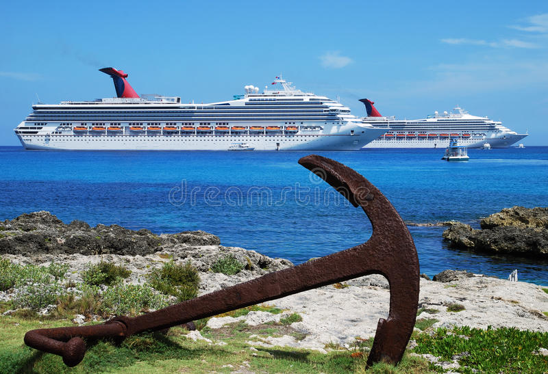 Grand Cayman Anchor. The view of a rusty anchor laying down on Grand Cayman shore with cruise liners in a background (Cayman Islands royalty free stock images