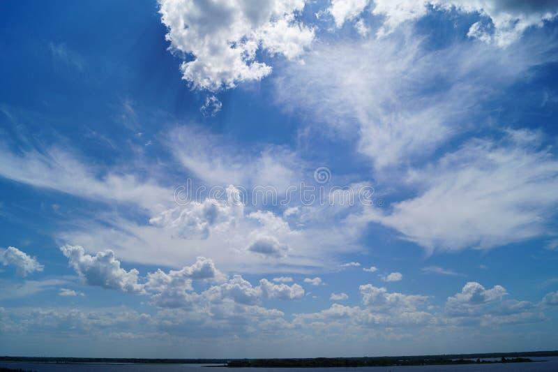 Grand ciel bleu vibrant avec les cluds et le hosizon de rivière photo stock