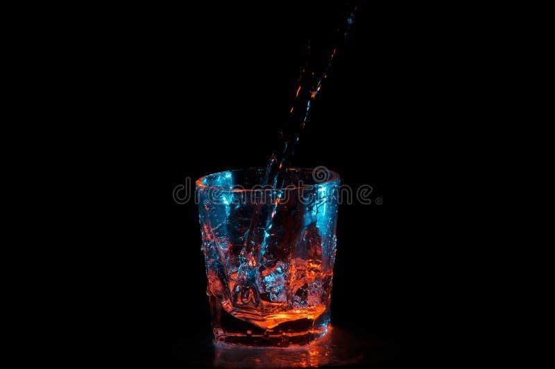 Grand courant d'eau étant versée dans un verre carré sous les lumières bleues et oranges d'isolement sur un fond noir images stock