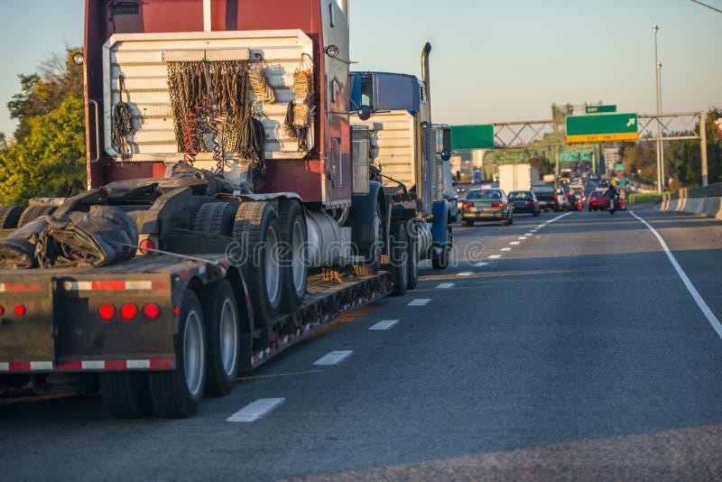 Grand d'installation camion semi transportant un autre semi tracteur de camion sur semi la remorque dévoltrice sur la route occup photographie stock libre de droits