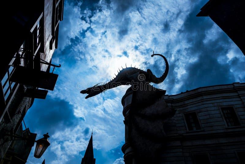 Grand dragon d'imagination apparaissant indistinctement au-dessus des maisons dans la ville magique antique dans la faible nuit o photographie stock libre de droits