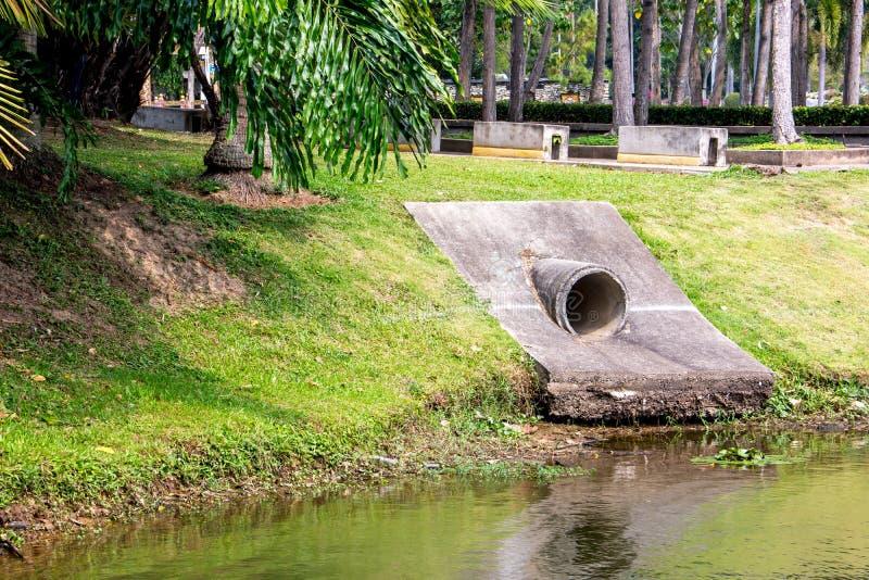 Grand drain d'égout de ciment dans le lac en parc photo libre de droits