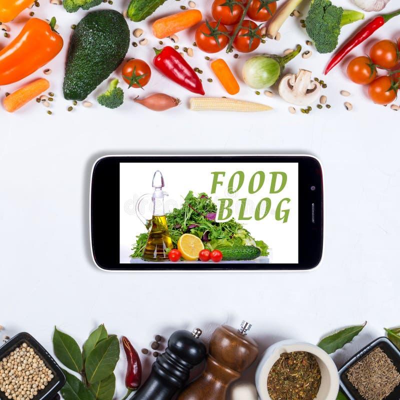 Grand ensemble de légumes, d'épices et de smartphone sur un fond blanc photographie stock