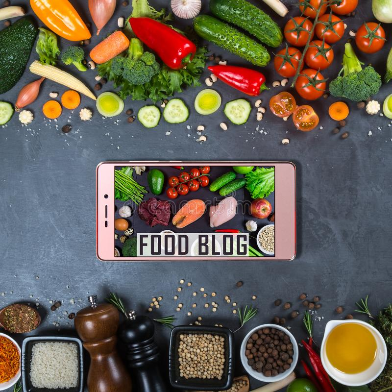 Grand ensemble de légumes, d'épices et de smartphone sur un fond noir image stock