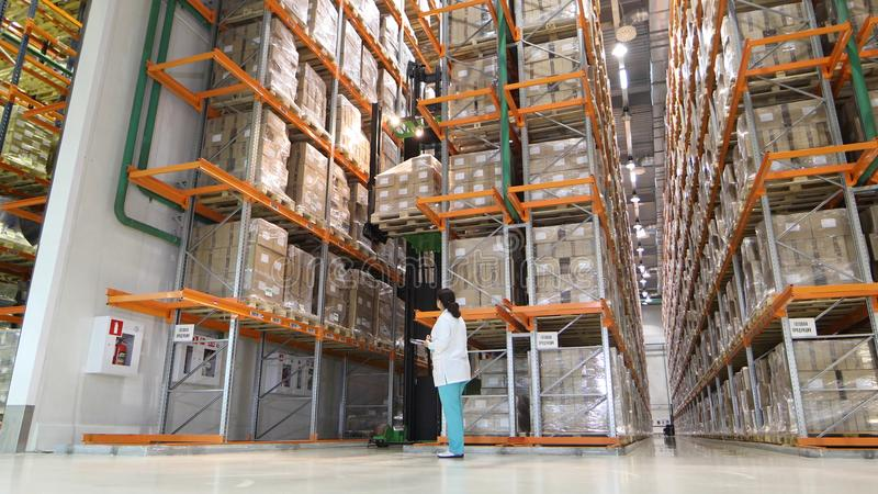 Grand entrepôt moderne avec des chariots élévateurs Entreposez le travailleur prenant le paquet dans l'étagère dans un grand entr photo libre de droits