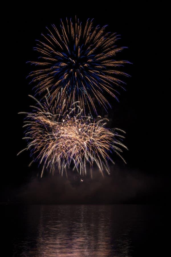 Grand or et étoiles bleues des feux d'artifice au-dessus du barrage de Brno avec la réflexion de lac photos libres de droits