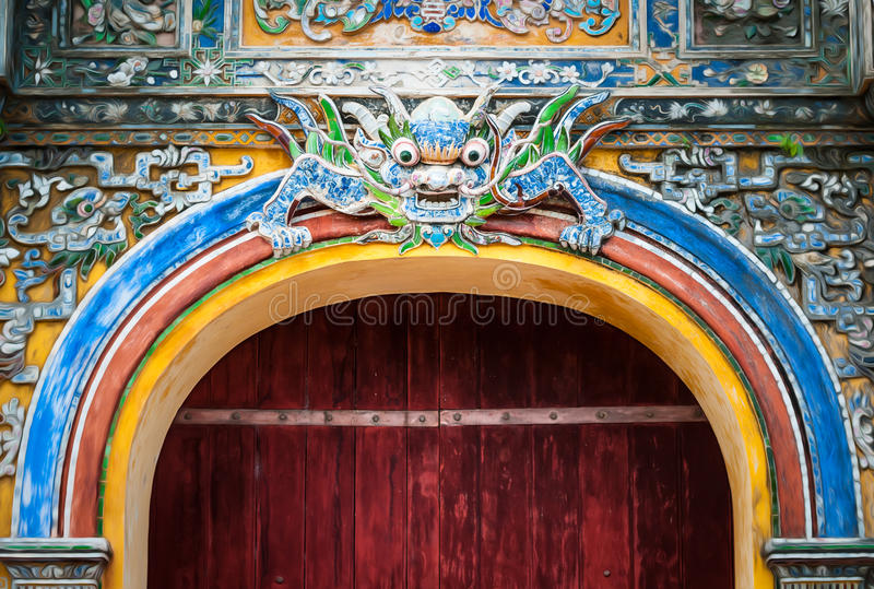 City gate in Vietnam with dragon pattern. Grand gate in dark wood and colorful decoration with traditional symbol, Hue City in Vietnam. Imperial arch entry stock photo