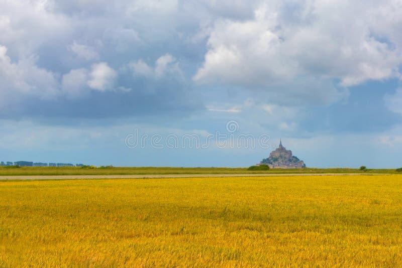 """Grand gisement jaune de graine de colza avec le ciel nuageux et le point de repère célèbre """"Le Mont-Saint-Michel """"à l'arrière-pla photos stock"""