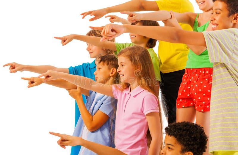 Grand groupe d'enfants dirigeant la vue de côté de doigt photographie stock