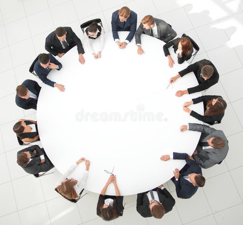 Grand groupe de gens d'affaires s'asseyant à la table ronde Le concept d'affaires images libres de droits