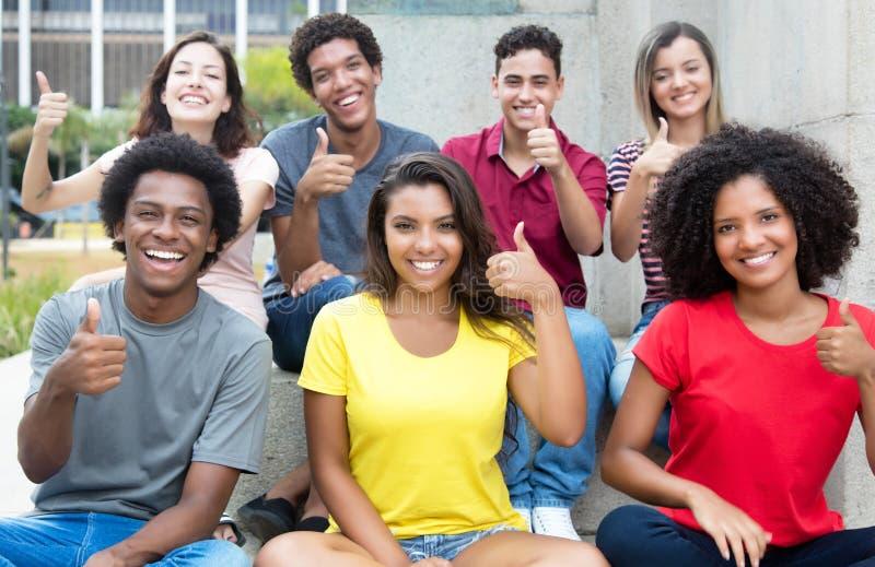 Grand groupe de jeunes adultes assez internationaux montrant le pouce u image stock