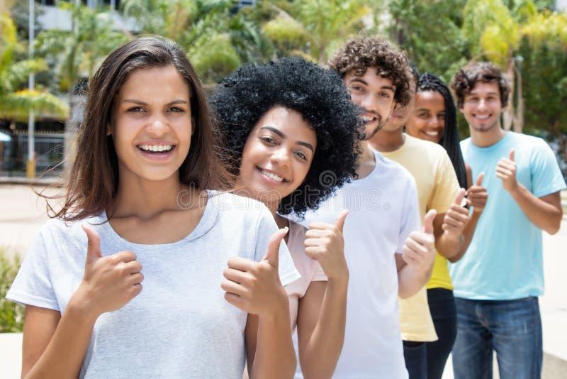 Grand groupe de jeunes adultes ethniques multi réussis dans la ligne images libres de droits