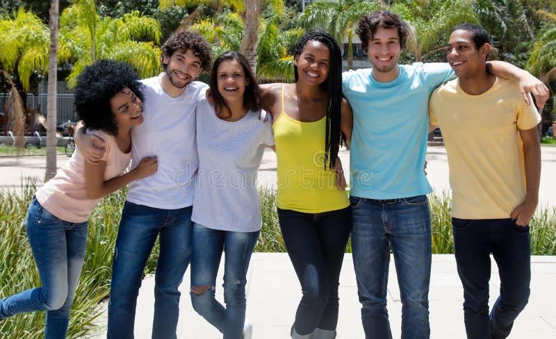 Grand groupe de rire les jeunes adultes internationaux image libre de droits