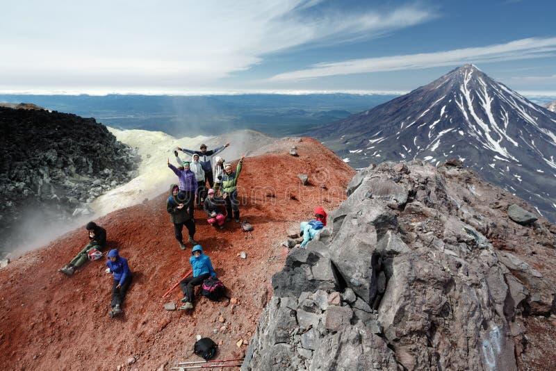 Grand groupe de touristes heureux en cratère de sommet de volcan actif photos stock