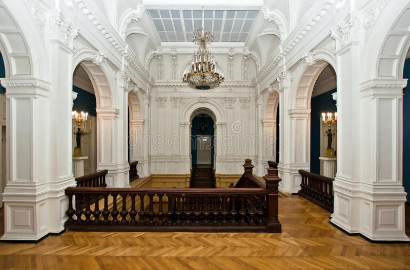 Grand hall in old majestic palace. With oak staircase stock image