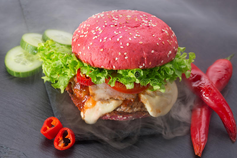 Grand hamburger rouge avec de la fumée sur une table d'ardoise images stock