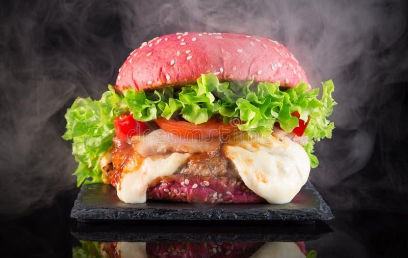 Grand hamburger rouge avec de la fumée sur une table d'ardoise image libre de droits