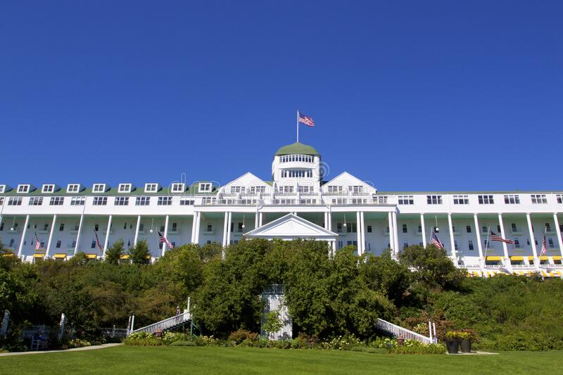 Grand Hotel   812504. The Grand Hotel facade with U. S. Flags flying under blue sky and stairs down to lawn on Mackinac Island Michigan  812504 stock images