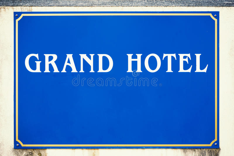 Blue grand hotel sign. Grand hotel sign on wall with copy space royalty free illustration
