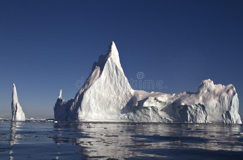 Grand iceberg avec quelques dessus outre de la côte images libres de droits