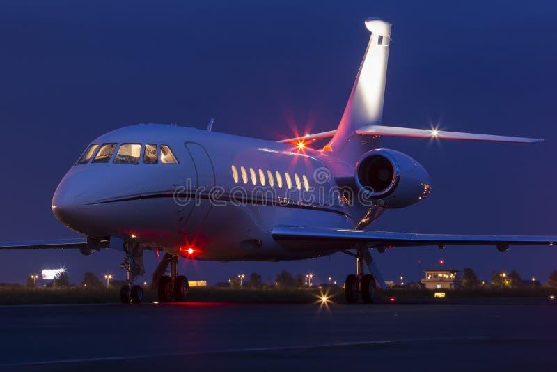 Grand jet moderne d'affaire privée prêt à décoller la nuit image stock