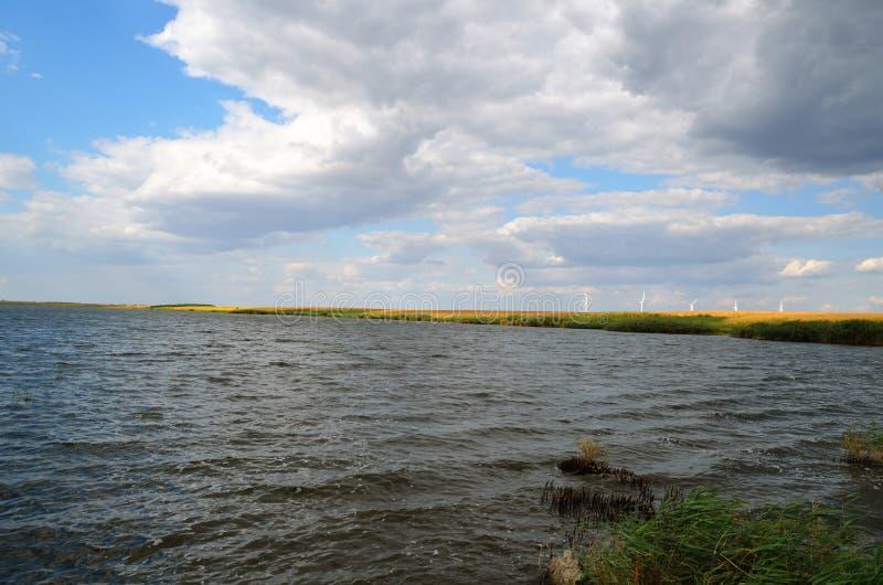 Grand lac avec la terre et grand ciel photographie stock libre de droits
