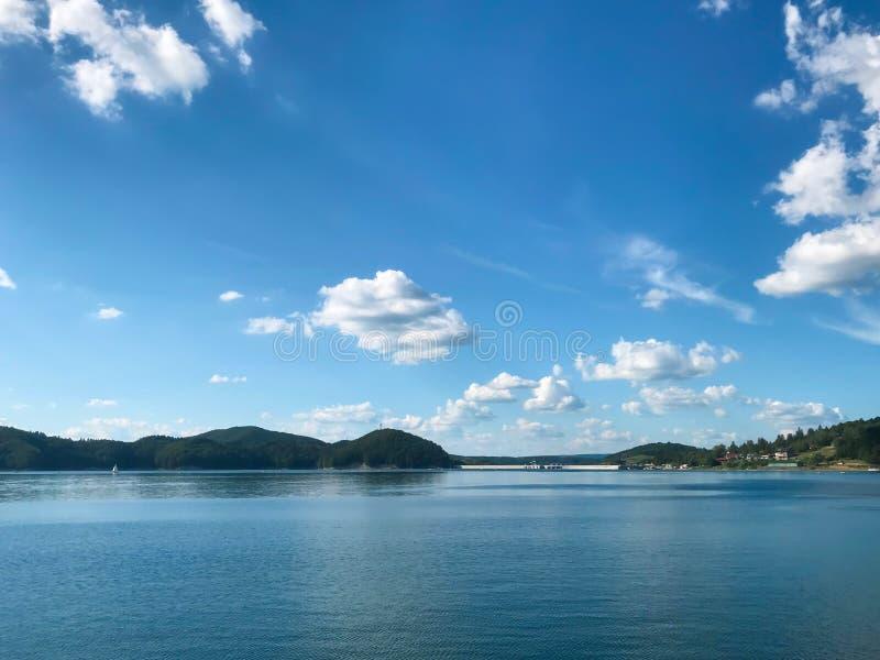 Grand lac en montagnes européennes Solina, Pologne Les grands, pelucheux nuages flottent à travers le ciel bleu images stock