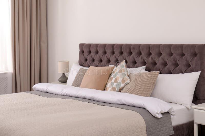 Grand lit confortable dans l'intérieur simple de chambre photographie stock