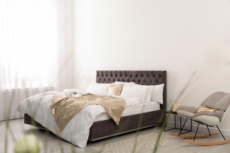Grand lit confortable dans la chambre élégante Intérieur moderne images stock