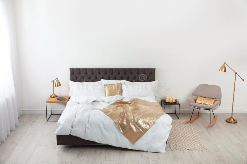 Grand lit confortable dans la chambre élégante Intérieur moderne photos stock
