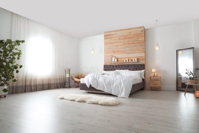Grand lit confortable dans la chambre élégante Intérieur moderne photo libre de droits