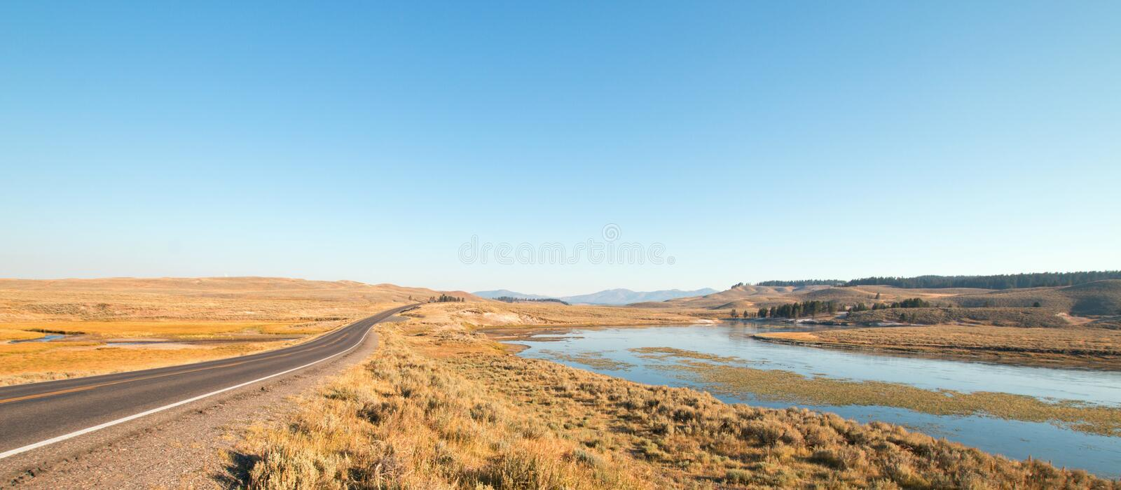 Grand Loop road next to bend in the Yellowstone river in the Hayden valley in Yellowstone National Park in Wyoming royalty free stock images