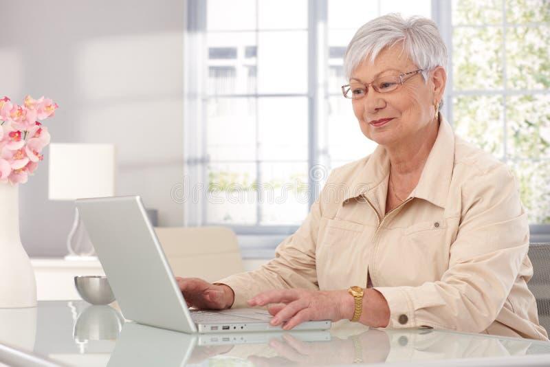 Grand-mère à l'aide de l'ordinateur portable à la maison photo stock