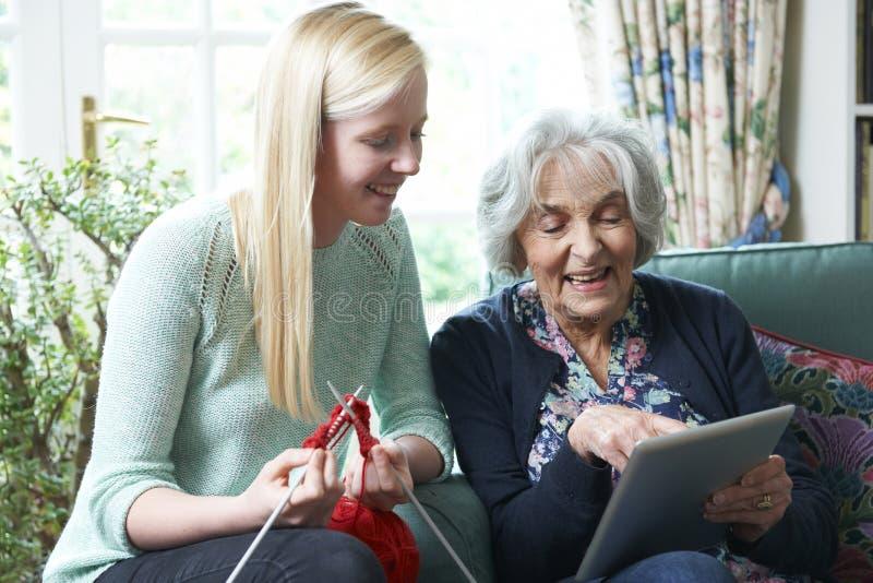 Grand-mère à l'aide de la Tablette de Digital comme Knits de petite-fille images libres de droits