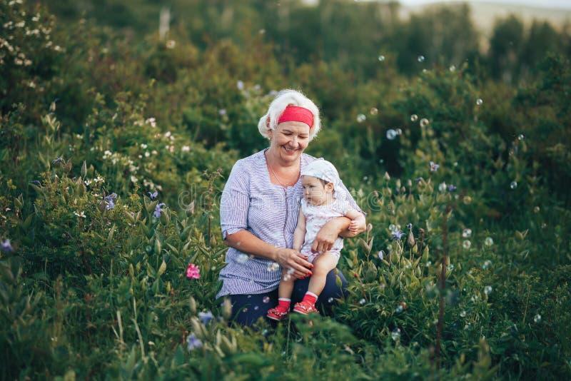 Grand-mère étreignant la petite-fille en nature dans le jour d'été ensoleillé photo libre de droits