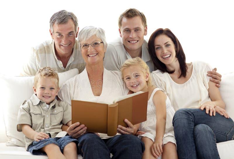 Grand-mère affichant un livre à son famille photographie stock libre de droits