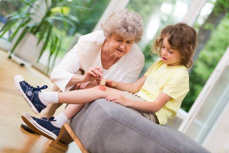 Grand-mère aidant avec un petit accident pendant le jeu images stock
