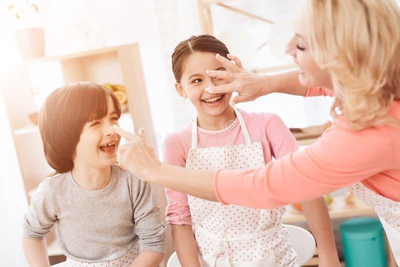 Grand-mère attirante enduite du nez de farine d'un petit-fils et d'une petite-fille joyeux dans la cuisine photos libres de droits