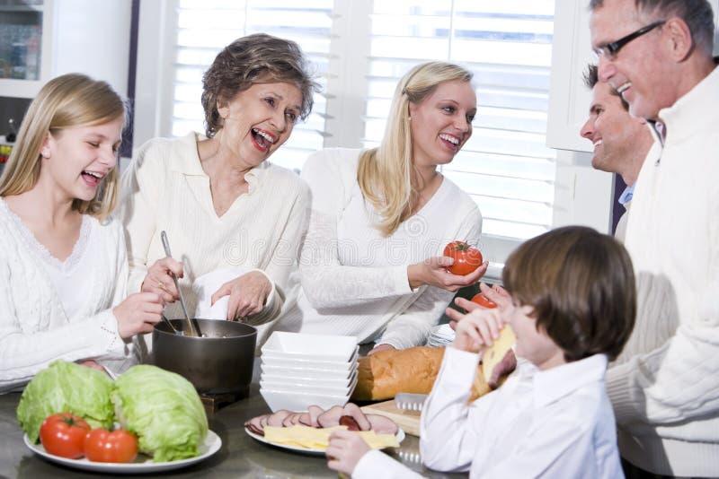Grand-mère avec la famille riant dans la cuisine photographie stock libre de droits