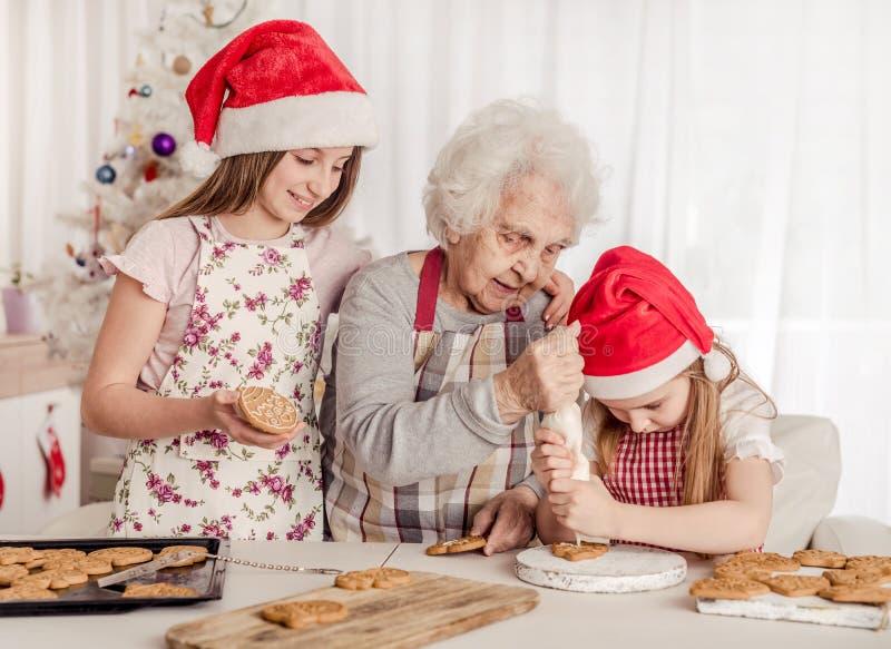 Grand-mère avec petites-filles tremper des biscuits à la crème avec de la crème images libres de droits