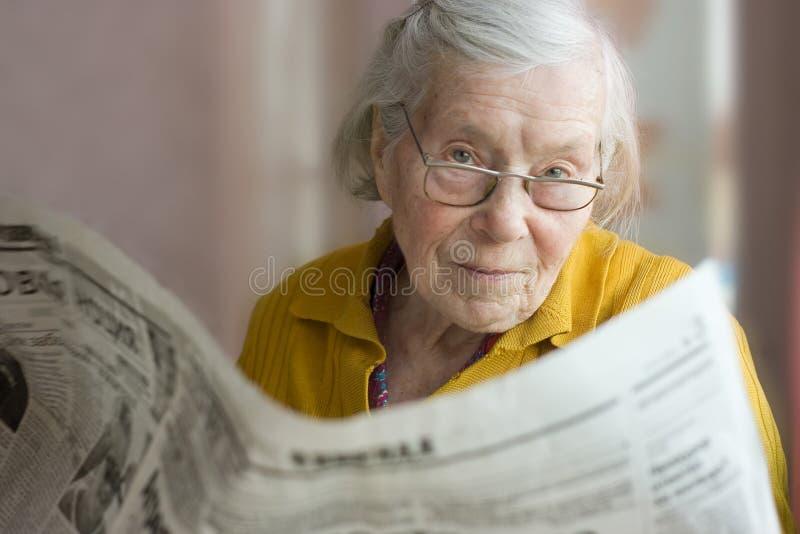 Grand-mère avec un journal image libre de droits