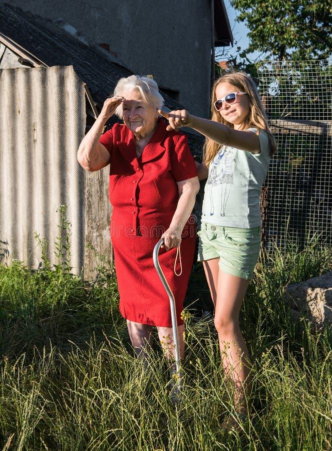 Grand-mère avec une canne et une petite-fille photo stock