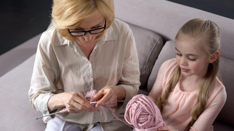 Grand-mère blonde tricotant avec sa petite petite-fille à la maison, fait main photographie stock libre de droits